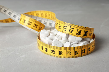 Weight loss pills with measuring tape on table