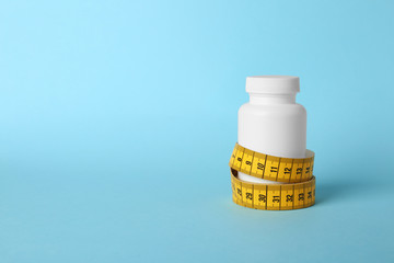 Bottle of weight loss pills with measuring tape on color background. Space for text