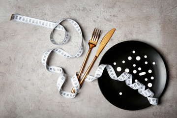 Plate with weight loss pills, cutlery and measuring tape on gray background, flat lay