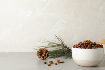 Bowl with pine nuts on table against light background. Space for text