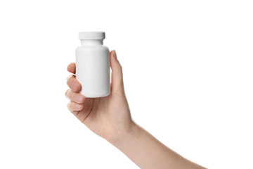 Woman holding bottle of pills on white background, closeup