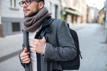 Young elegant man with backpack walking in the city.