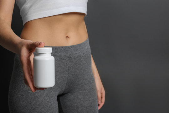 Slim woman holding bottle of weight loss pills against gray background, closeup. Space for text