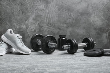 Composition with dumbbells and fitness accessories on floor. Space for text