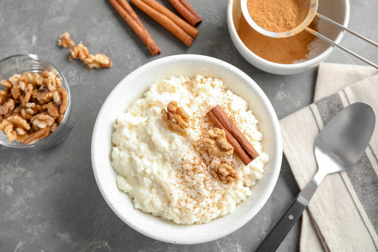 Creamy rice pudding with cinnamon and walnuts in bowl served on grey table, top view