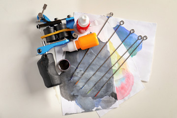 Tattoo machine, needles, ink and sheets of paper on white background, top view