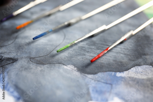 Tattoo needles with ink on painted paper, closeup\