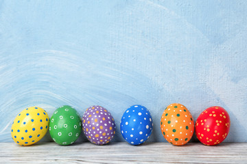 Decorated Easter eggs on table near color wall. Space for text