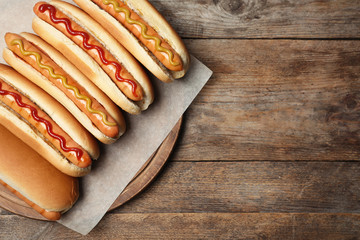 Tasty fresh hot dogs on wooden table, top view. Space for text Wall mural