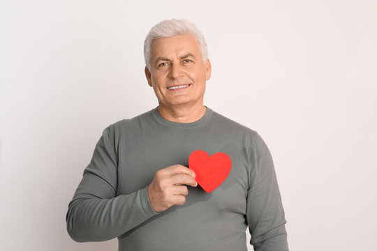 Happy mature man holding red paper heart on white background
