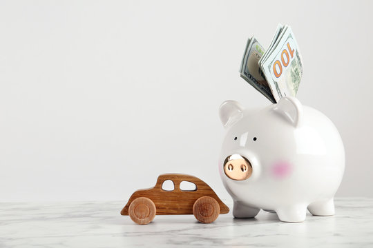 Piggy bank with dollar banknotes and toy car on table against white background. Space for text