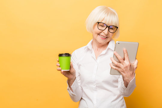 Happy senior woman using tablet while drinking coffee isolated over yellow background.