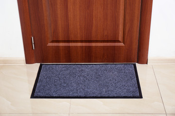Modern welcome mat at door in hall