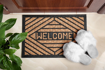 Welcome doormat and white slippers at door in hall, top view