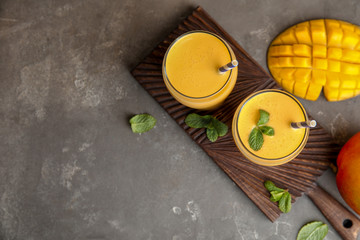 Glasses of fresh mango drink and fruits on table. Space for text