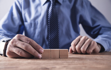 Businessman holding wooden cube on a wooden table.