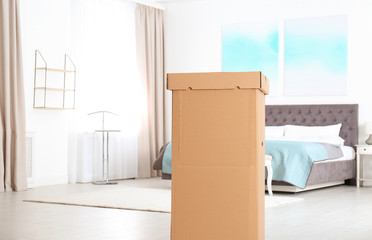 Cardboard wardrobe box in bedroom. Space for text