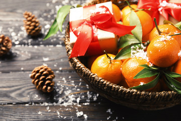 Bowl with ripe tangerines, Christmas gift and artificial snow on wooden table, closeup. Space for text