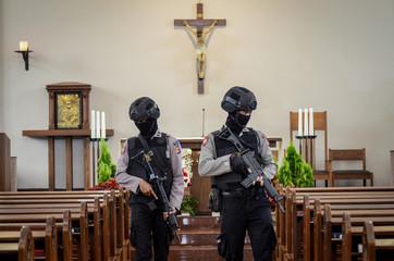 Policemen walk as they check inside Ignatius Church ahead of Christmas celebration in Cimahi