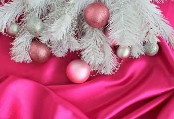 Christmas toys-balls on the branches of a white spruce on the background of shiny pink silk. Background, texture, card, greeting