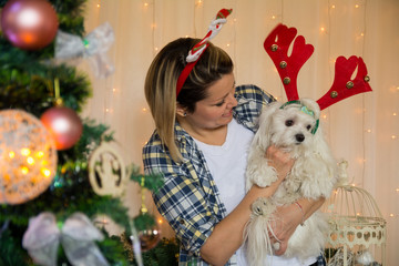 Women holding cute little white dog with cute christmas decoration on her had