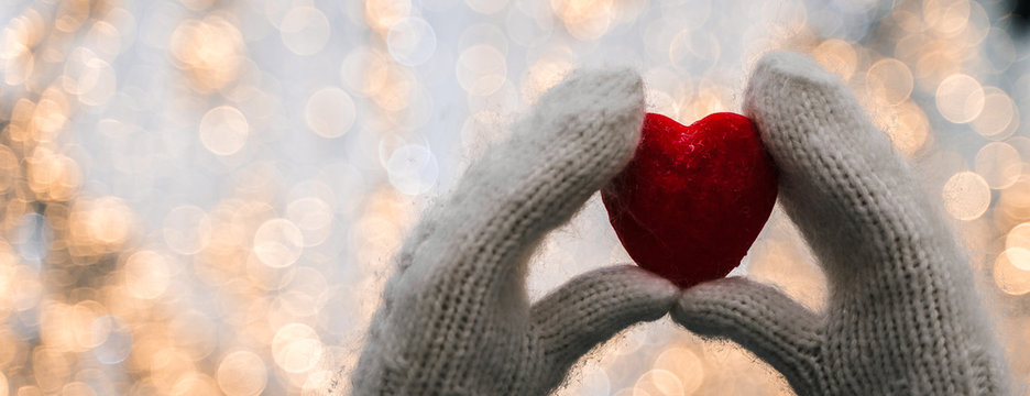 Female hands in knitted white mittens with heart of snow in winter day. Love and St. Valentine cozy concept, copyspace, bokeh background, banner