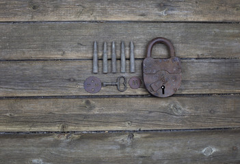 old lock with keys on wooden background