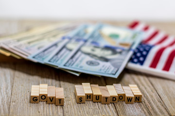 Government Shutdown USA concept with American flag and money bills on white background and wooden board