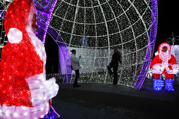 People pose for a picture inside a giant illuminated Christmas ball in the Christmas Lunapark in Limassol