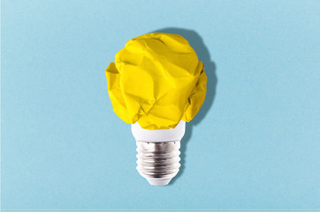 Wall Mural - light bulb from crumpled yellow paper on a blue background, concept idea