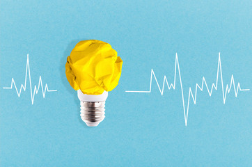 Wall Mural - crumpled yellow paper light bulb near to a cardiogram on a blue background, concept idea