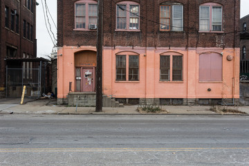 Red brick building with orange paint in industrial urban area with concrete sidewalk