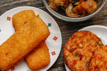 Crispy breaded fried fish fillet, vegetarian burger made from various type of vegetables and grilled champignons mushroom on old wooden table