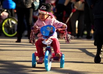 A child rides a tricycle received during the annual gift-giving event organised by the Fire Department, in which they hand out items donated throughout the year to children in need, in Ciudad Juarez
