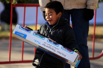 A child reacts after receiving a toy during the annual gift-giving event organised by the Fire Department, in which they hand out items donated throughout the year to children in need, in Ciudad Juarez