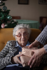 Excited Grandmother Receiving Christmas Gift From Granddaughter At Home .