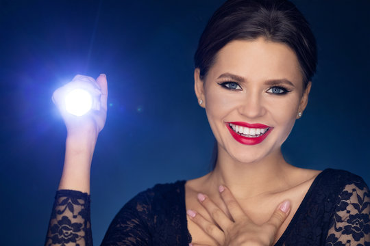 the girl with the led flashlight in her hands shines straight. the girl laughs, surprised and glad that you have found. glare of light and dark Studio background. portrait of a beautiful model who