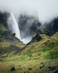 Person standing near beautiful waterfall in Iceland.