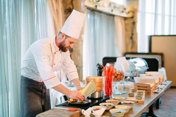 Breakfast. The chef prepares eggs for Breakfast.