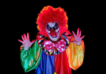 Horror clown making scary gestures against black background