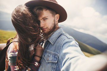 Happy hipster couple making selfie on top of windy mountains. Stylish sensual couple in love taking selfie photo and having fun. Travel together and Wanderlust concept.
