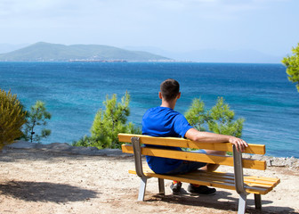 The guy in the blue T-shirt sits alone on a wooden bench on a dais against the background of the Mediterranean Sea in Greece. Sunny summer day, a young guy on a bench on the coast