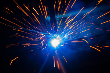 Spark of the electric welding with the sparks of burning hot metal..