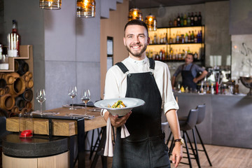 A handsome young guy with a beard dressed in an apron standing in a restaurant and holding a white plate with a moth. Against the background, the bar counter and the loft style interior