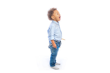 A little dark-skinned boy with curly hair in jeans and a light shirt is standing in profile holding pencils in his hands looking to the side and shouting
