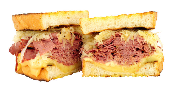 Pastrami Reuben style sandwiches with sauerkraut and melted Swiss cheese isolated on a white background