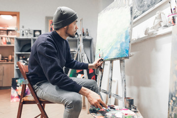 Portrait of an artist student sitting in class and painting a painting on canvas. Education at art school. Man learns painting.