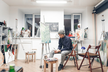 Young professional artist sits on a chair near an easel with a host in a cozy creative studio and paints an oil painting. Creative atmosphere in the home studio of painting. Interior