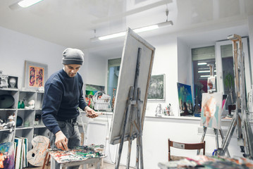 Young, positive artist works, paints a picture of oil paints in a cozy studio. Artist with a canvas on an easel places an oil paint on a palette. Process of creating a picture. Copyspace