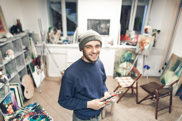 Portrait of a smiling student of art school stands on the background of the studio, looking into the camera.Smiling teacher of painting on the background of art studio.Happy artist in his own studio.